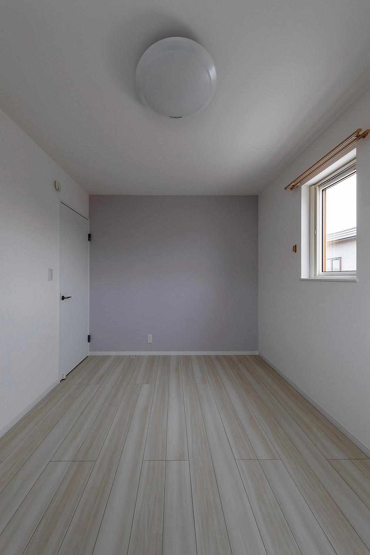 子ども部屋は、淡い紫色のアクセントウォールをあしらったシンプルな内装。大型収納を設けて、汎用性の高い個室に