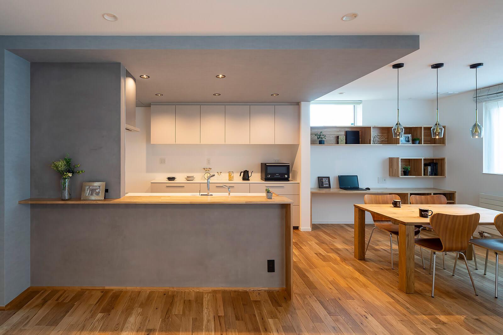 対面式のキッチンは、下がり天井とキッチンカウンターのリビング側をグレーの塗装仕上げに。マットな質感が上質さを演出している