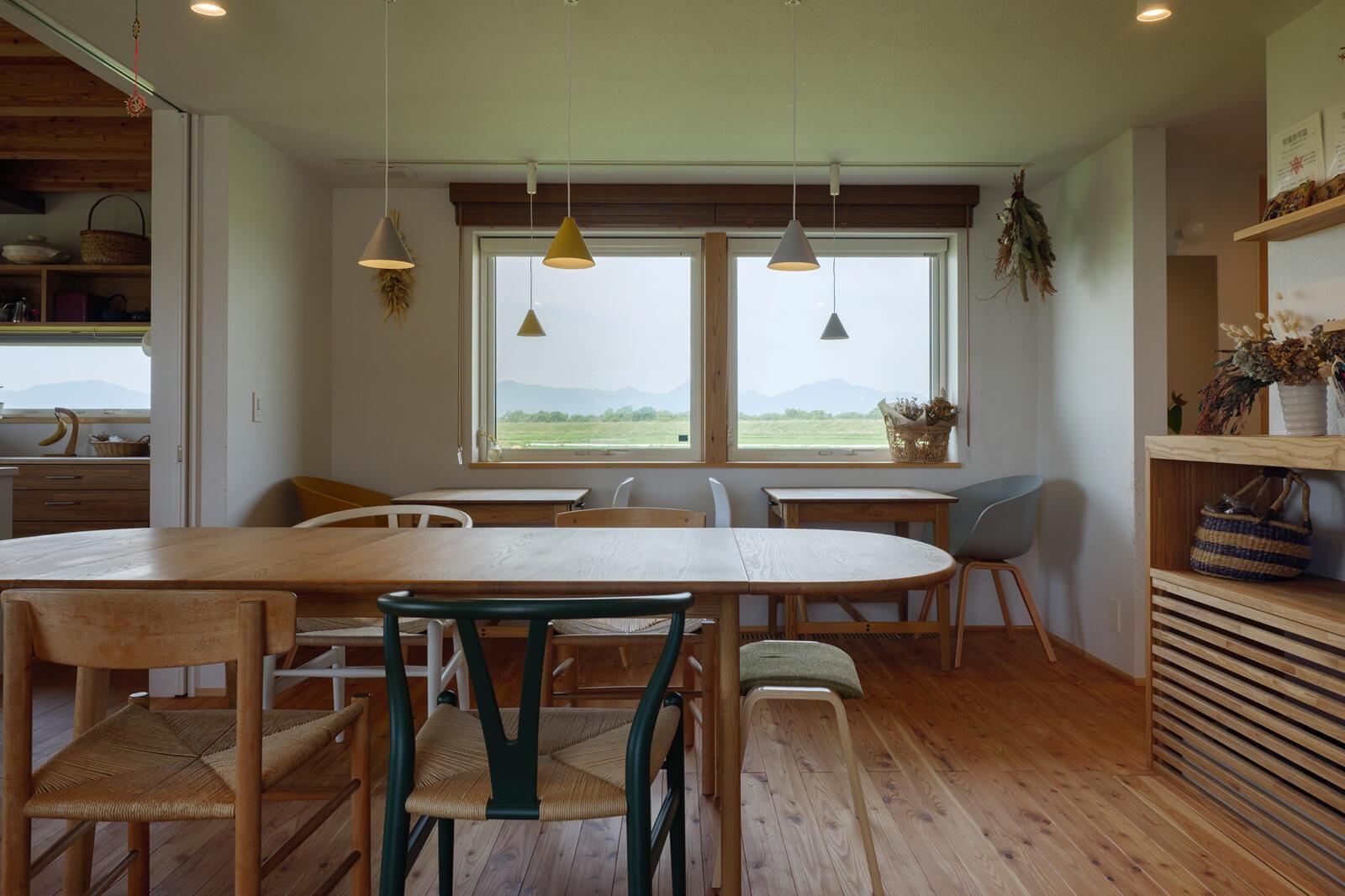 かわいらしいペンダントライトが彩るダイニング兼カフェスペース。自然素材の心地よさを五感で感じることができる空間。右手のスリットの床下にエアコンが設置されている