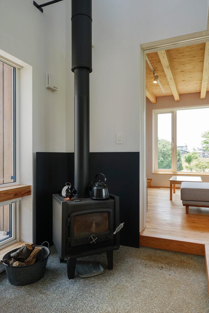玄関土間に置かれた薪ストーブ。冬場は薪ストーブを主暖房、床下エアコンを補助暖房として使用。揺らめく炎が心も癒やしてくれる