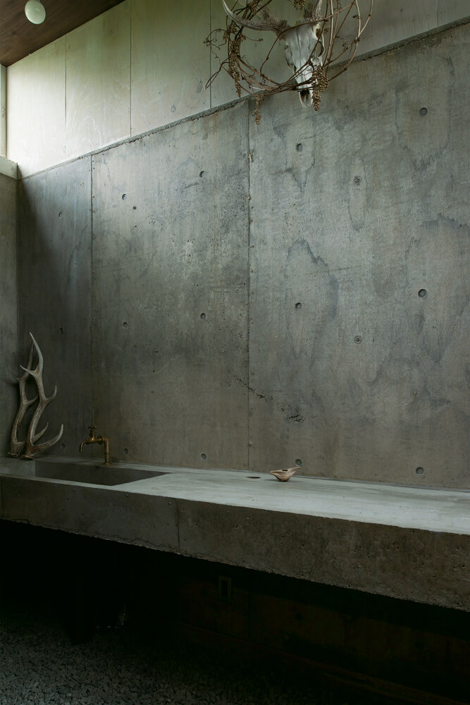 B1階のウチ庭は、アウトドア帰りの汚れ落としなどがしやすいようRC打ち放しとモルタル造作の洗面が設けられている
