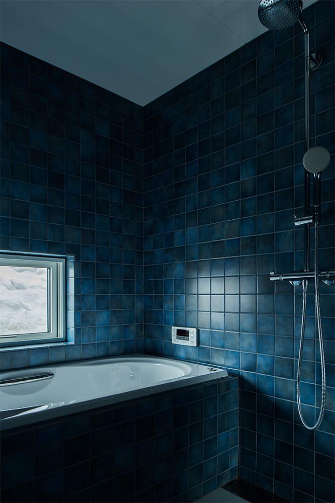 1枚1枚ニュアンスの異なる深い青色が美しいタイルで仕上げたバスルームに、心も身体もリラックス