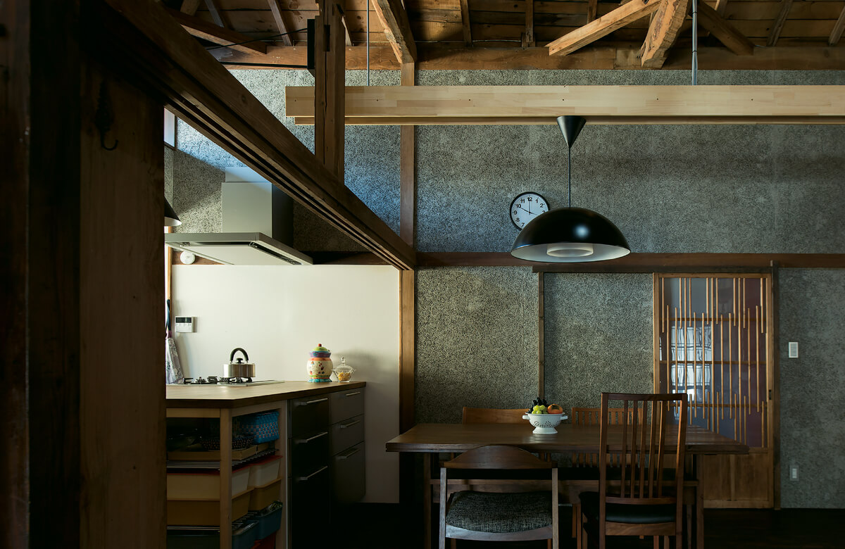 元の家の間取りを活かしたダイニング・キッチン。断熱性・吸音性に優れた木毛セメント板の壁が古民家にマッチする
