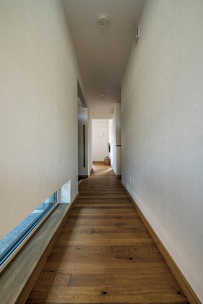 玄関から2つの個室へ延びる廊下には、地窓を採用。細長い開口からこぼれる外光が足元をやさしく照らす