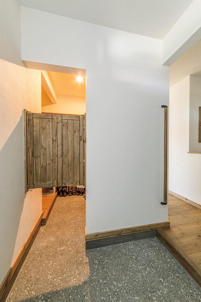 造作スウィングドアを設けたシューズルームは水まわり、パントリー、キッチンへと動線がつながっている。シューズルームの隣は、洗面スペース。木製扉やタイルが可愛い洗面台も造作仕様