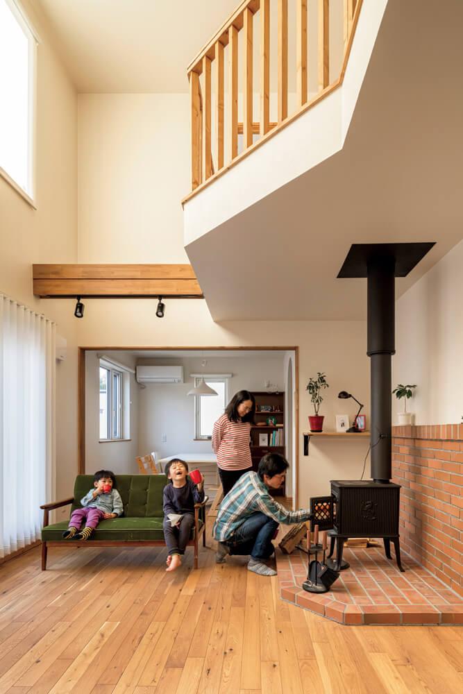 薪火の温もり満ちる開放的なリビングのアクセントになっている2階手すりは、ツーバイ材の造作。足触りの良い床はナラ無垢材にした。薪ストーブは、実家でも愛用しているヨツールのシガータイプを採用。ストーブの下に設えられた給気口が、薪火の燃焼を助けている