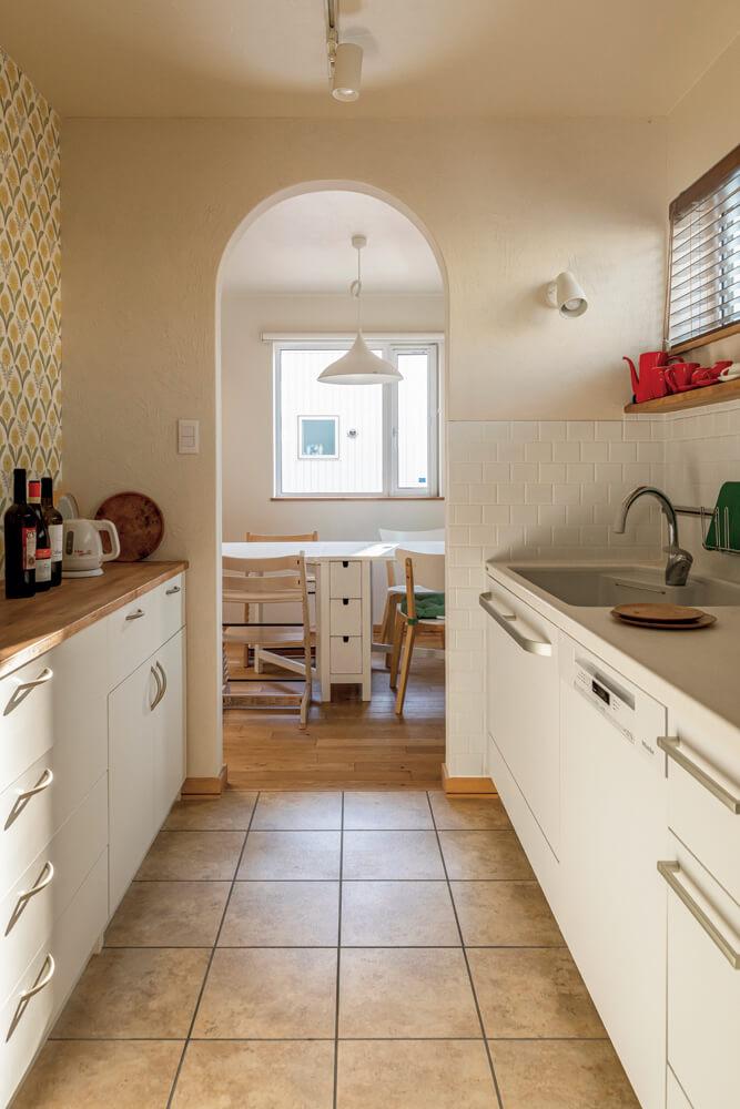 キッチンからダイニングを見る。アールをつけたキッチン出入り口は、塗り壁仕上げ。床は、メンテナンスしやすいフロアタイルを張った