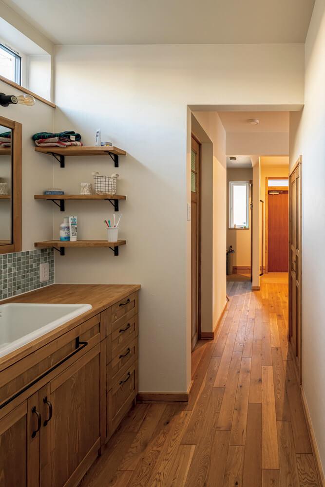 奥さんの希望で脱衣室と分離した洗面室は、採光窓とタイルやパイン材、バーチ材などを用いた造作洗面台を設けた。右手扉は階段下収納