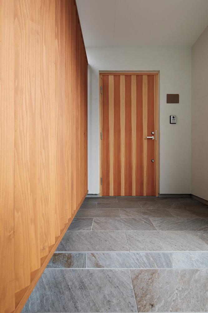 ゆったりとした玄関ポーチ。木製ルーバーが外部からの視線を遮る役割を果たしている