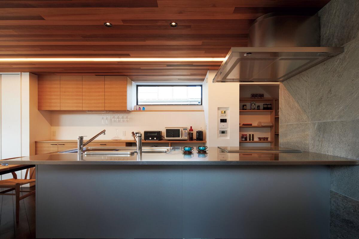 LDKの顔となるトーヨーキッチン製のアイランドキッチン。心地よい間接照明使いにも注目を
