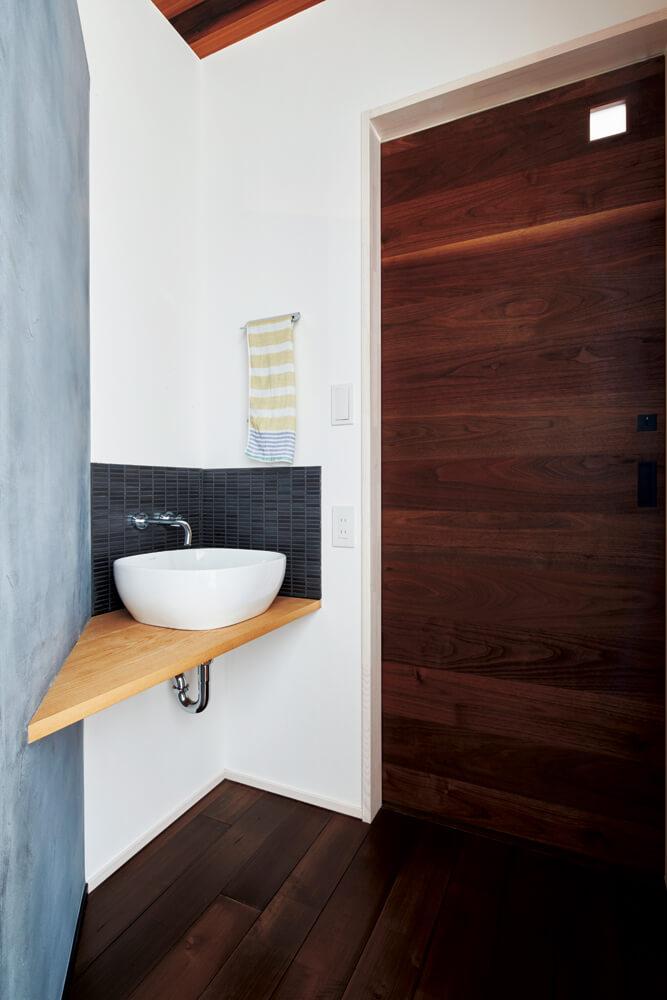 玄関ホールのグレーの壁の裏側に、帰宅後すぐに手洗いやうがいができるよう、手洗いボウルを設置。右手扉の先がトイレ