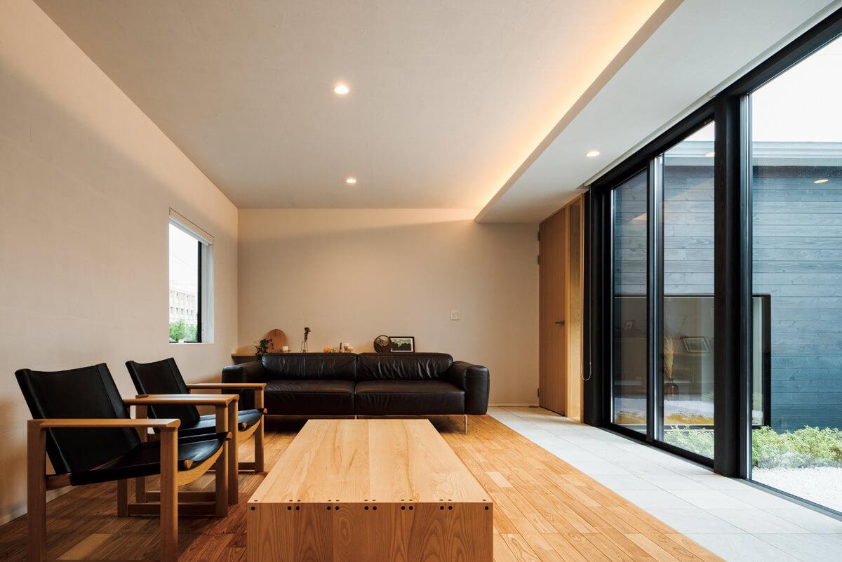 リビングの壁はグレーの顔料を混ぜた漆喰の塗り壁を採用。落ち着いた印象の室内を間接照明が照らし、より一層上質な雰囲気に
