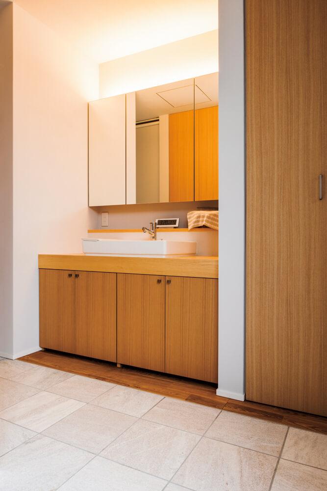 ご夫妻のための洗面所。収納や建具はすべて造作で、床と同じタモ材を張り、室内に統一感を持たせている