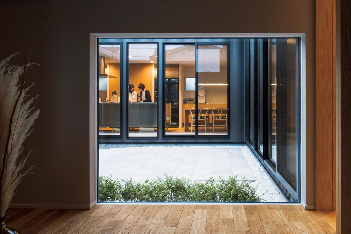 玄関ホールの地窓は110㎝高。砂利と石英でローメンテナンスに仕上げた中庭から、室内に光を導く