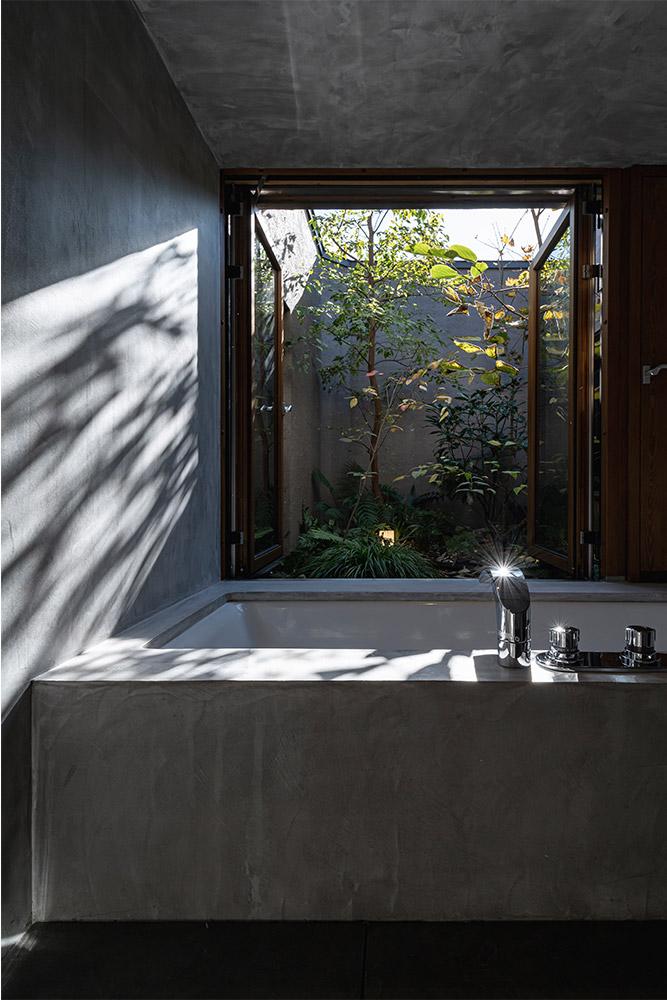 モールテックスで仕上げた特別感あふれるバスルーム。内装の素材感や坪庭の植栽が目を楽しませてくれる
