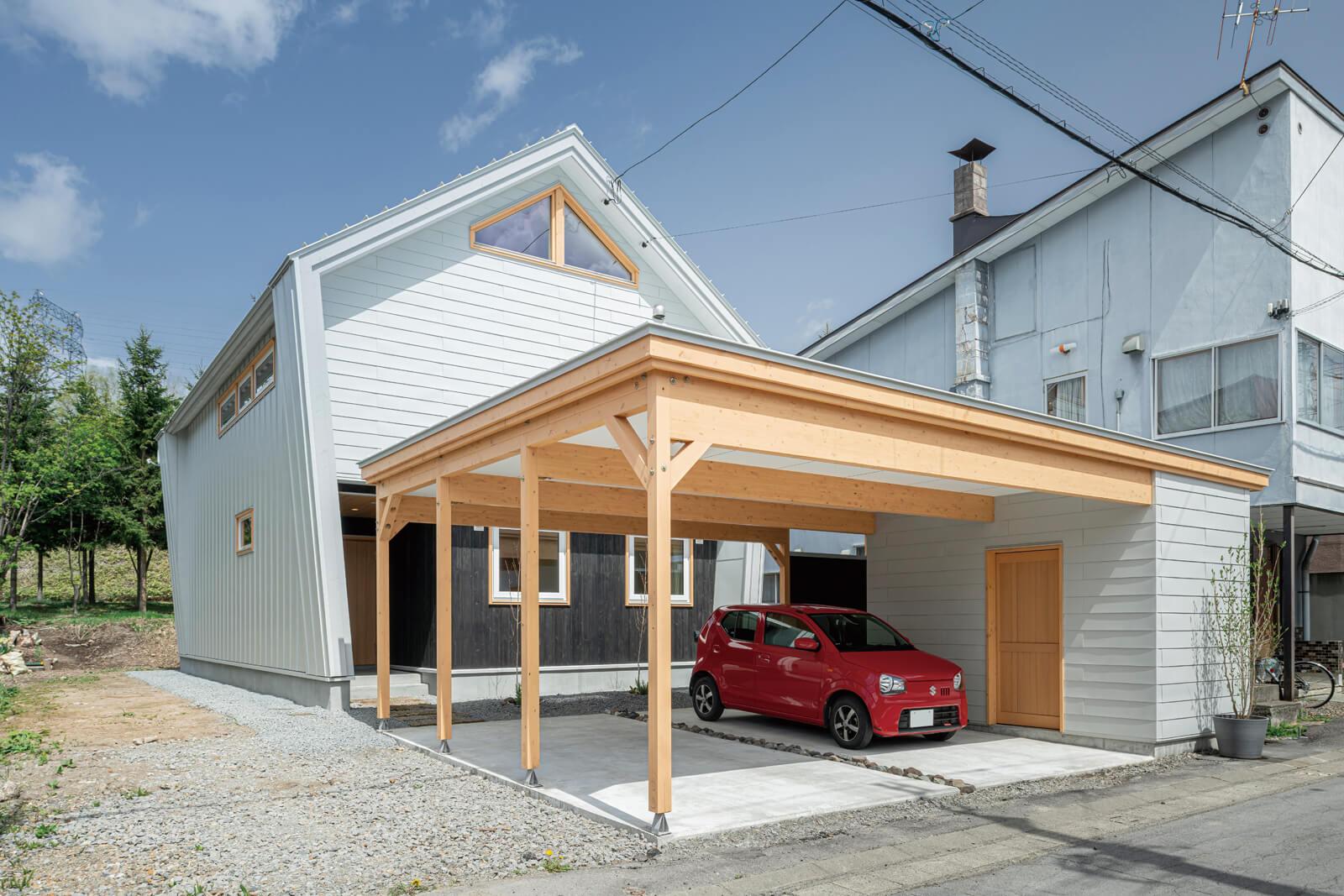 グレーホワイトのガルバリウム鋼板と道南スギでアクセントをつけた五角形の外観。ビックサイズのカーポートは、外観とイメージを合わせて車2台・物置・駐輪スペースを確保した