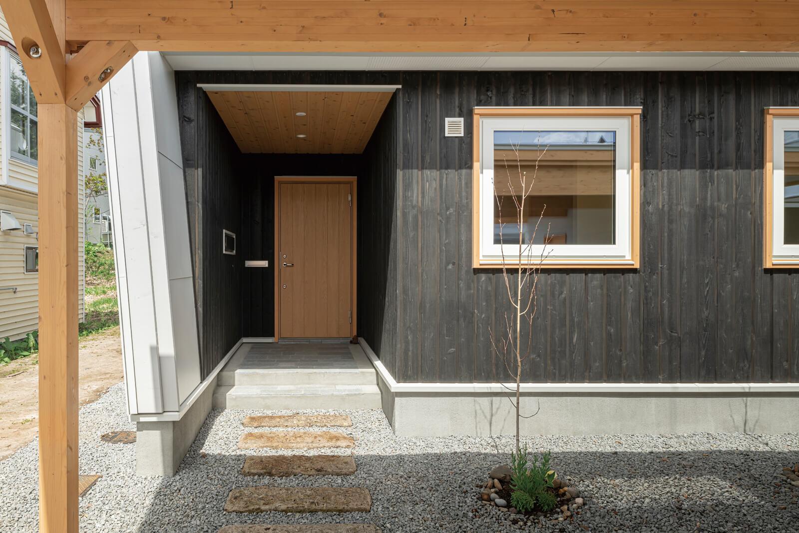 ナチュラルパイン・道南スギ・札幌軟石の敷石と素材感を楽しめる玄関アプローチ