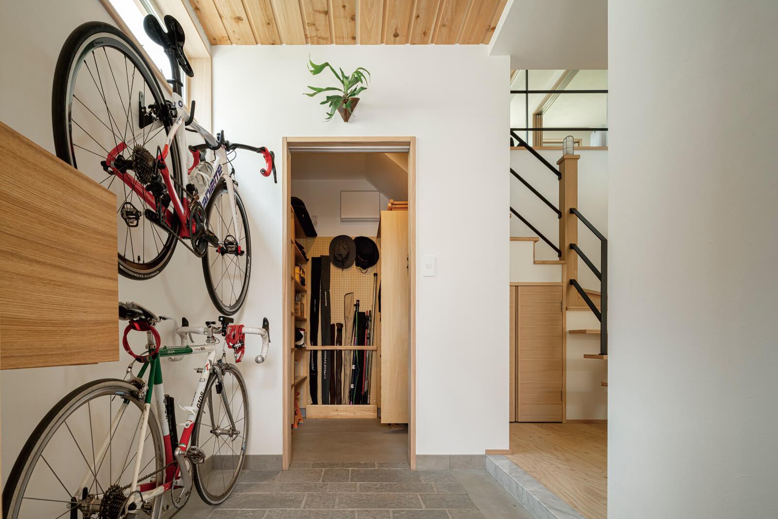 靴やアウターのほかアウトドアグッズなども収納できる大容量のシューズクロークを併設した玄関。趣味のロードバイクは壁面に収納できるようにした