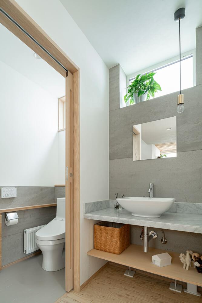 1階トイレの手洗いは、帰宅後の手洗いも兼ねてホールに設置した。天板は大理石を使用してメンテナンスも楽に