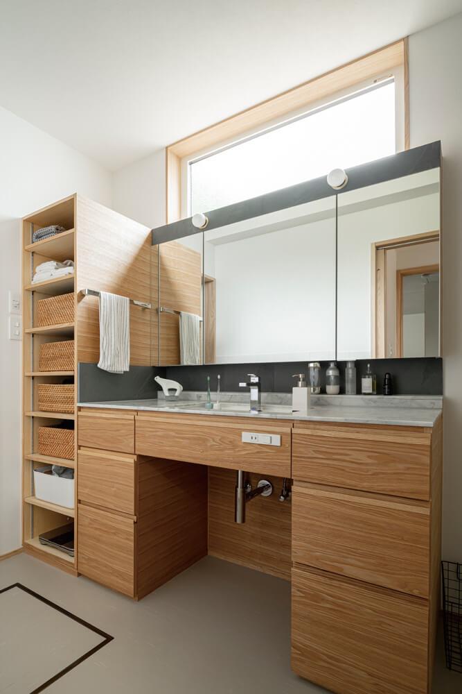 1階のユーティリティにはメインの造作洗面台。二人が立っても余裕のある幅で、バスタオルなどの収納も造作。大理石とブラック系の石材を組み合わせ、キャビネットのタモオイル仕上げとマッチしている