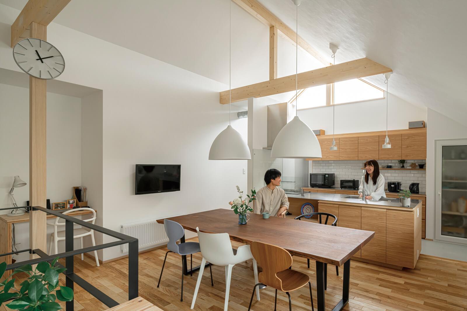 フルオープンのキッチンは、ウッディな背面収納と一枚板のステンレス天板の組み合わせ