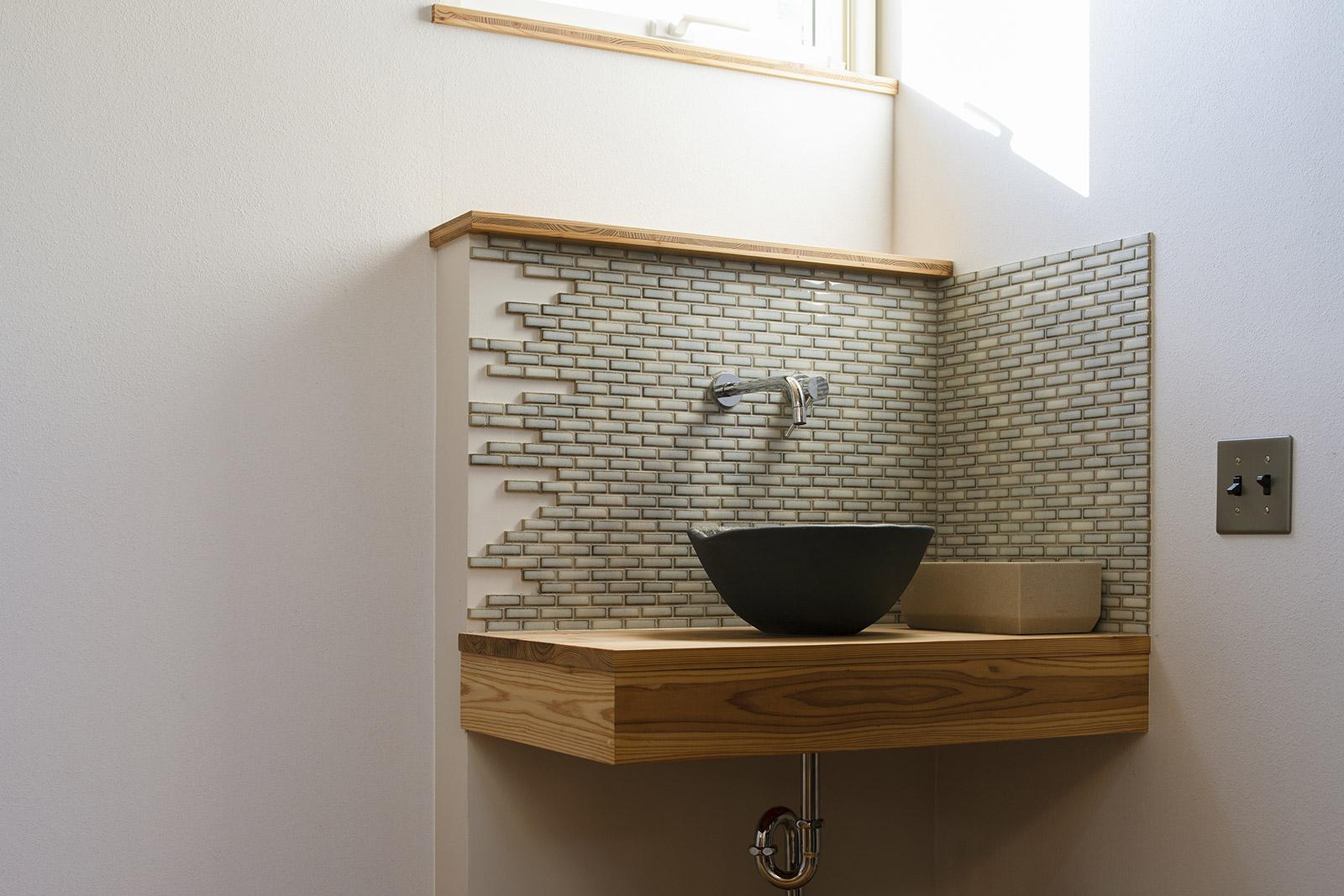 玄関ホールには、帰宅後にすぐ手が洗える手洗い場を設けた。陶製ボウルやタイルが木質感あふれるホールのアクセントにもなった