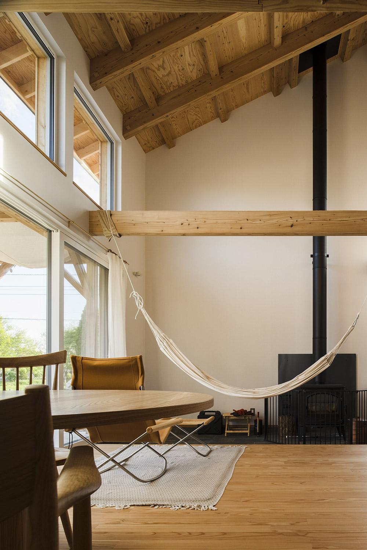 カラマツ材の構造現しの天井、梁、床が温かくのびやかな空間をつくるリビング・ダイニング。しっかりとした梁にはKさん念願のハンモックを吊って