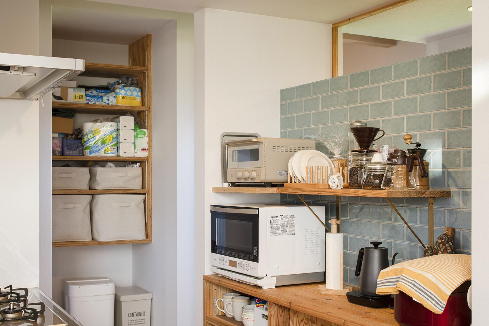 家電やキッチン用品のレイアウトから考えた造作背面収納。施工時により使い勝手を良くするために壁付け棚板の奥行きを一部調整した
