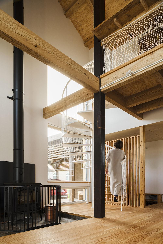 リビングの螺旋階段横に立つ黒い親柱は、カツラの古材。「武部建設の提案で採用した梁材ですが、これぞ大黒柱という佇まいが気に入っています」(Kさん)