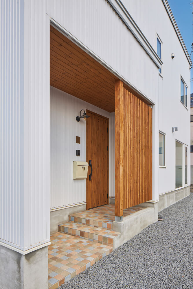 やわらかい色味のタイルをモザイク状に敷いた玄関ポーチ。木の板張り天井と縦格子でよりナチュラルに