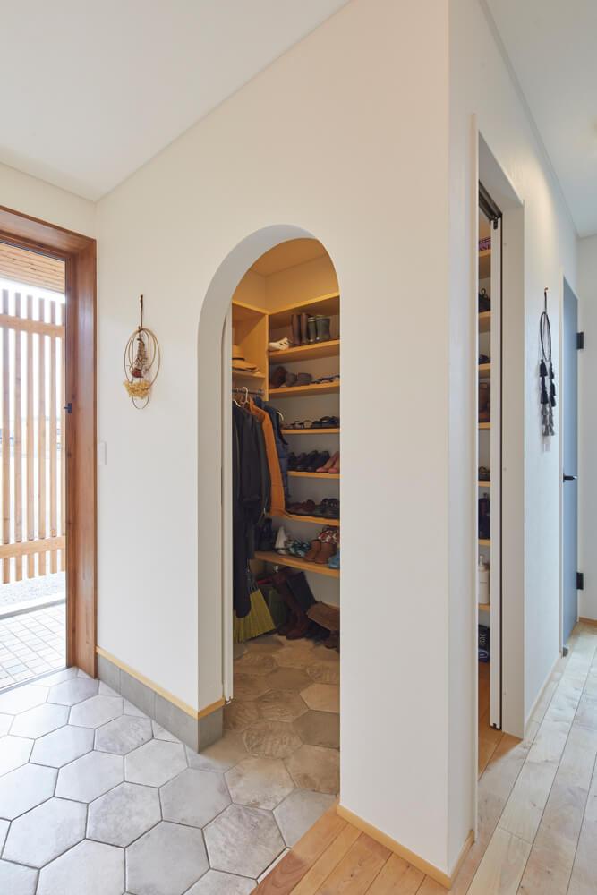 玄関横のシューズクロークの入り口はアーチ型に。床はハニカムタイルでアクセントをつけた