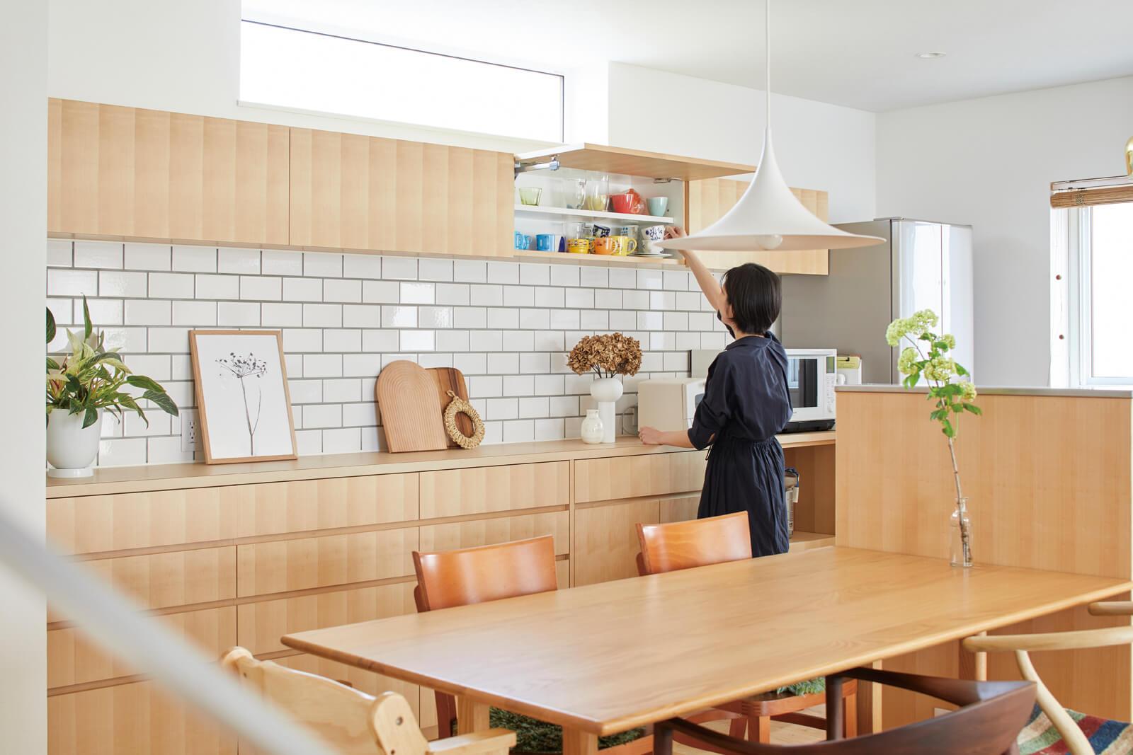 3600㎜の大容量キッチン収納はこだわりのひとつ。キッチン用品だけでなく書類や文具も収納してスッキリと。キッチン本体を囲うように設置した腰壁は座った目線からでも隠れるように高めに調整した