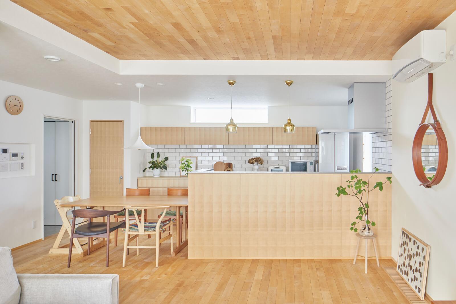 木目が美しく映えるキッチン全景。腰壁や収納建具の木目感は何度も相談を重ねたポイント
