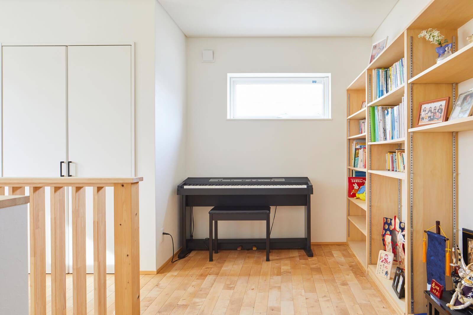 2階フリースペースには家族共用の大容量本棚とピアノスペースも設けた