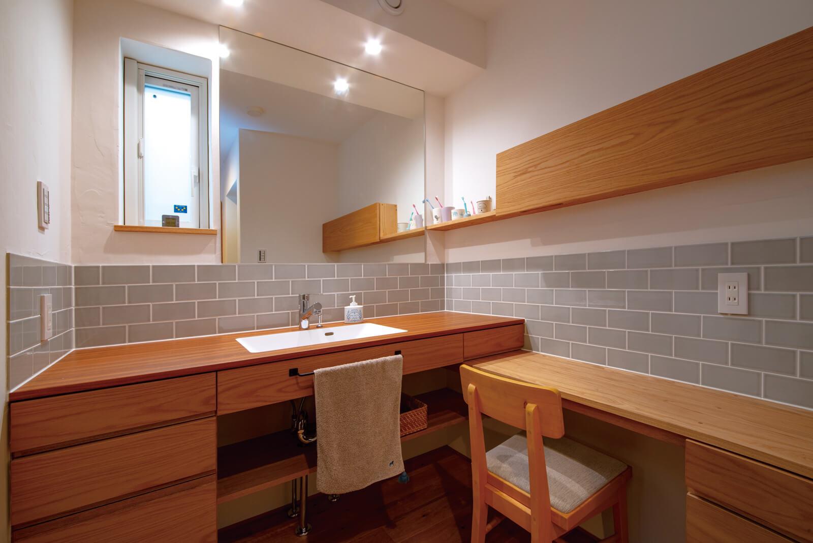ゆとりある洗面室は、タモ材やタイルを用いた造作仕様。いつでもすっきりとした空間が楽に保てるよう、引き出しや扉付き収納も多く設けられている
