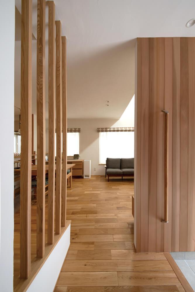 レッドシダーを張った玄関ホールは、シームレスでリビング・ダイニングに直接つながる。木製パーテーションの奥は、段差を緩やかに整えた階段