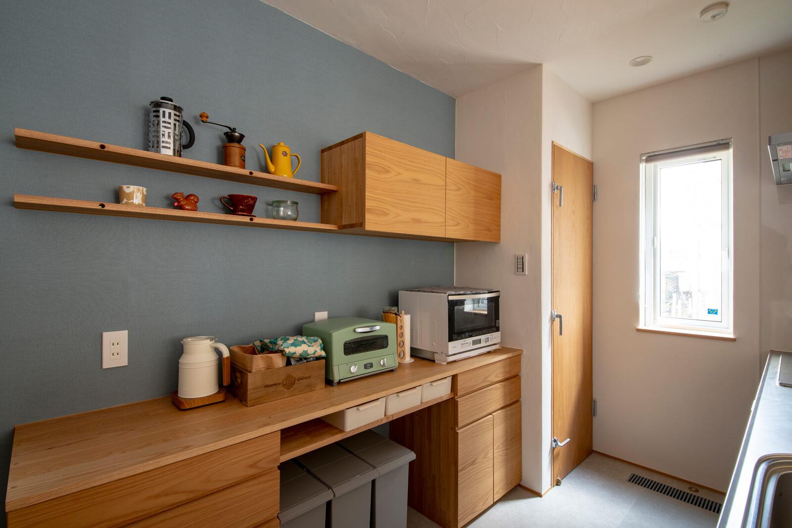 ブルーグレーのアクセントウォールと造作背面収納、食品庫を採用したキッチン。通路幅を広く取ってあるので、夫婦でキッチンに立っても、ストレスフリーで作業ができる