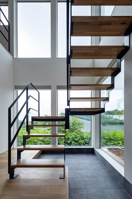 家族用玄関は吹き抜けに。軽やかな階段と大きな窓の向こうに緑と空が見えて開放感抜群