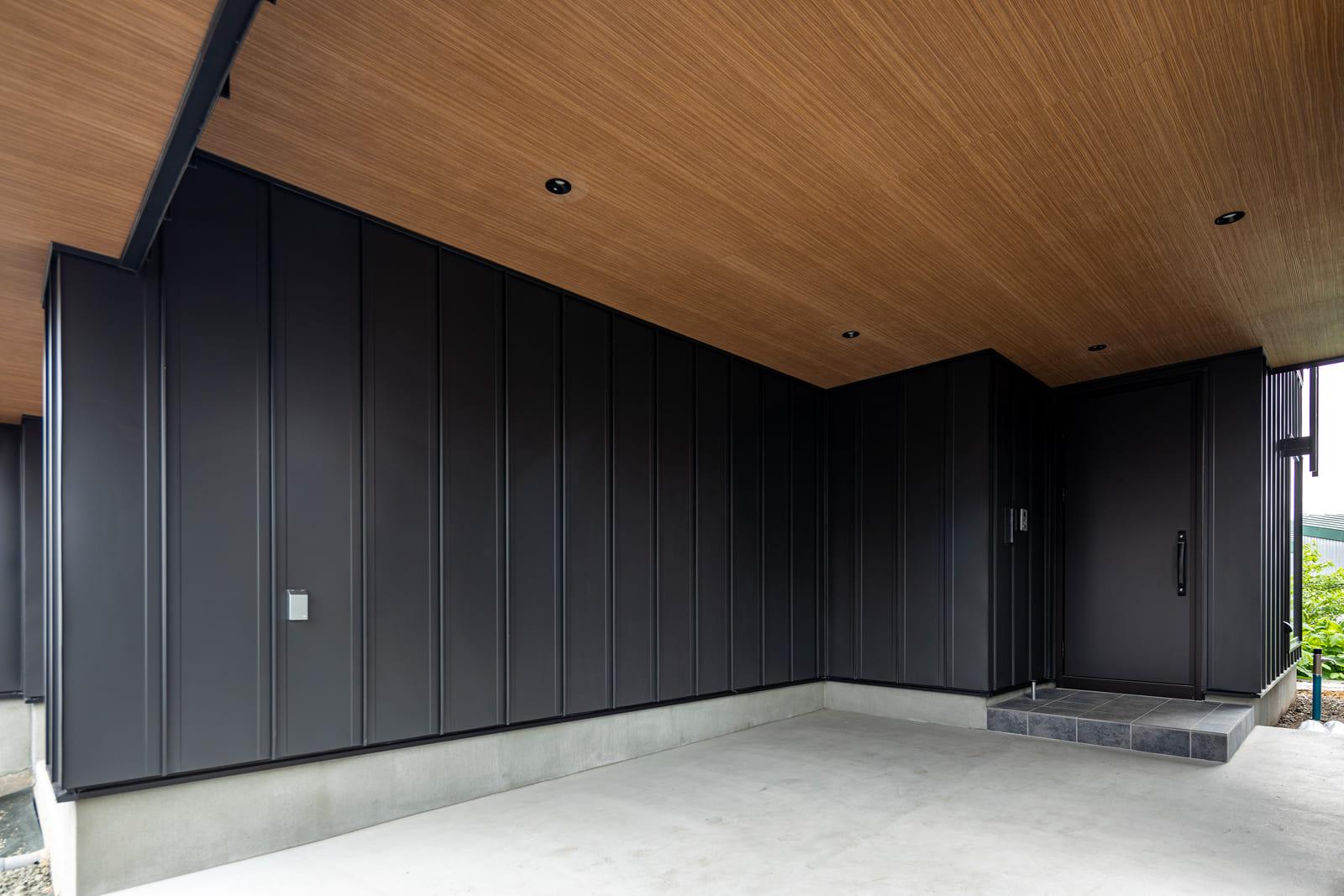 屋内ガレージに1台と玄関前の計2台分の駐車スペースを確保。天井には木調の軒天材を採用
