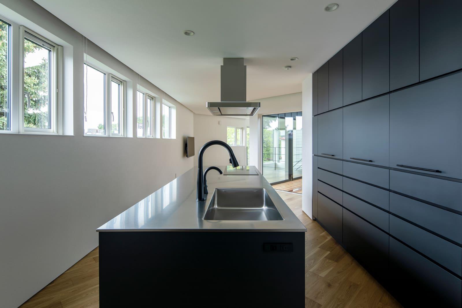 敷地形状に合わせ斜めに配置したアイランドキッチンは、家電類も背面収納に収めてすっきり。つや消しの黒で統一したキッチンは、蛇口も黒に