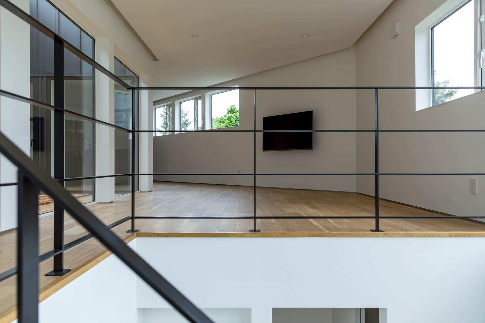 階段を上がるとLDKと光の庭が目に入る。斜めの壁がうまくキッチンを目隠ししてくれる