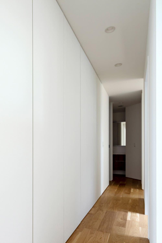 一見すると壁に見えるが実は一面、天井までの大型収納。家族それぞれにスペースを割り振れる