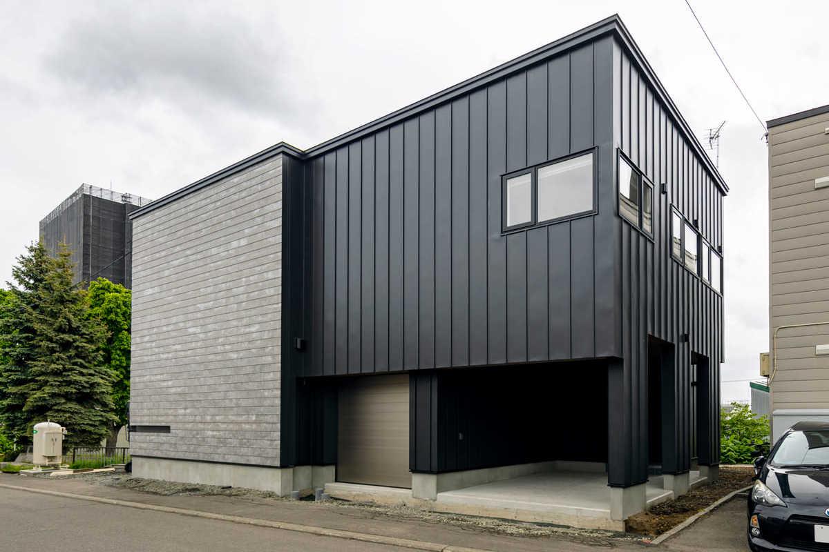 黒のガルバリウムが印象的な外観。人通りの多い道路側にはほとんど窓を設けず、プライバシーを確保した。事務所側の外壁は黒のガルバリウム鋼板に、セメント素材の風合いを生かした「ソリド」を鎧張りに