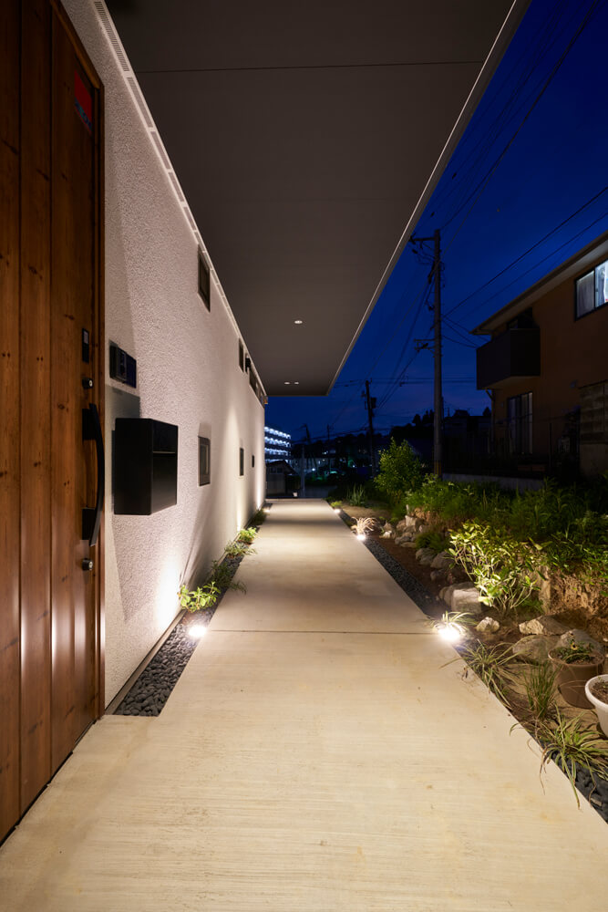夜になると、玄関から外壁に沿って伸びる軒下の通路を照明が明るく照らす