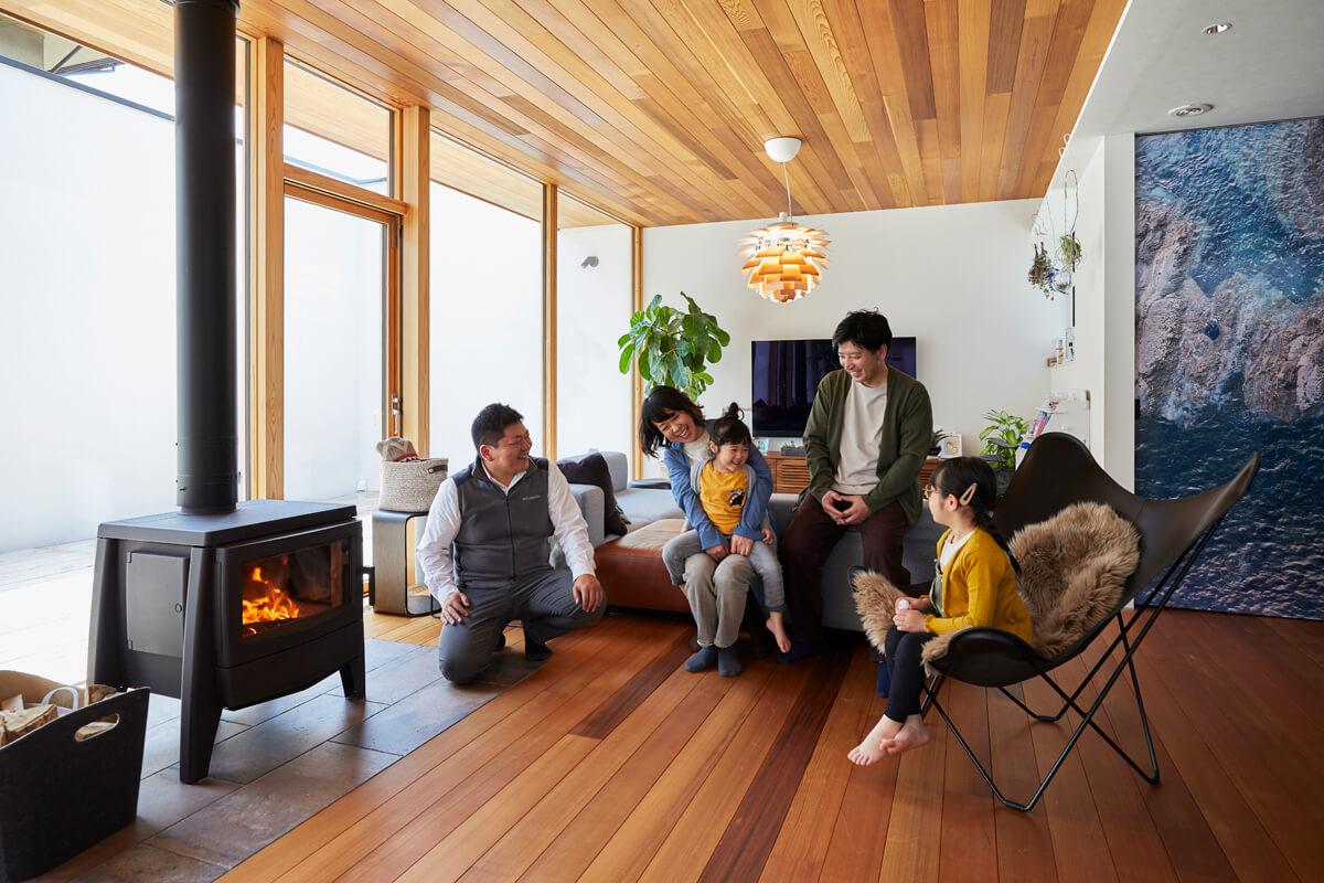 談笑するAさんご一家とdld山形ショールームの佐藤伸之さん。佐藤さんはAさん宅の薪ストーブライフを支える大切なパートナーだ