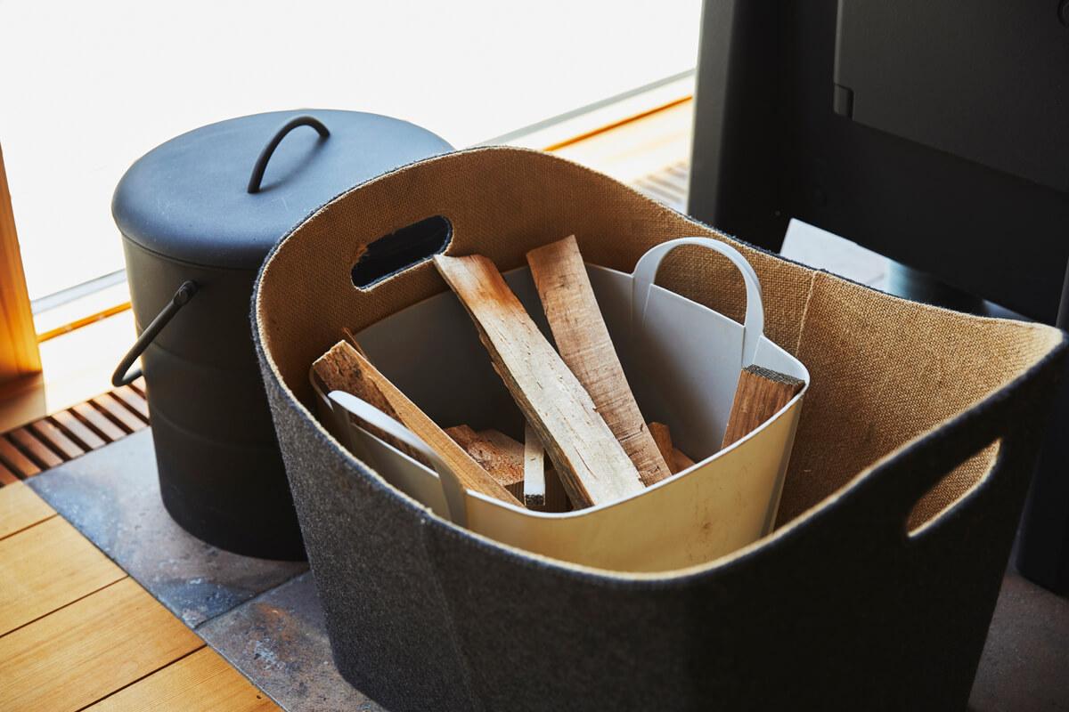 薪ストーブの横には着火用の端材をストック。灰取りバケツは薪ストーブの質感に合わせたマットな風合いのものをセレクト
