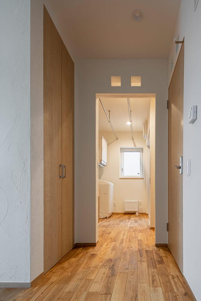 玄関ホールから見たユーティリティ。造作の収納棚を多めに配置して、衣類に関する家事作業がすべて完結する仕組み