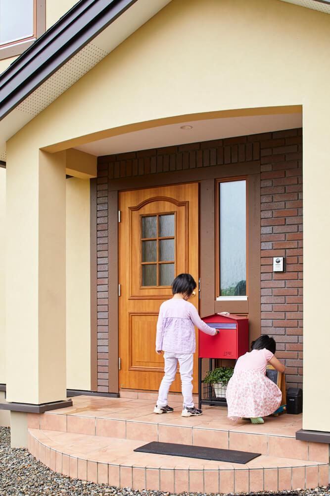 レンガ張りの壁をアクセントにした表玄関。木質感あふれるドアは、断熱性に優れたスウェーデン製