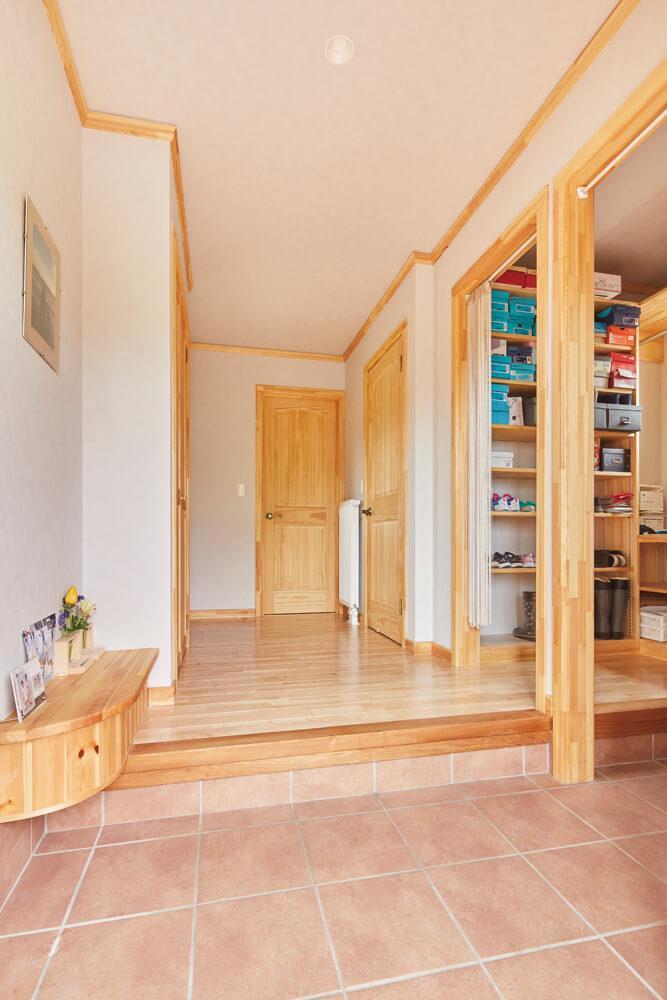 土間続きに大容量のシューズクロークを設けたゆったり仕様の表玄関。正面の扉は、水まわりや農家玄関につながっている