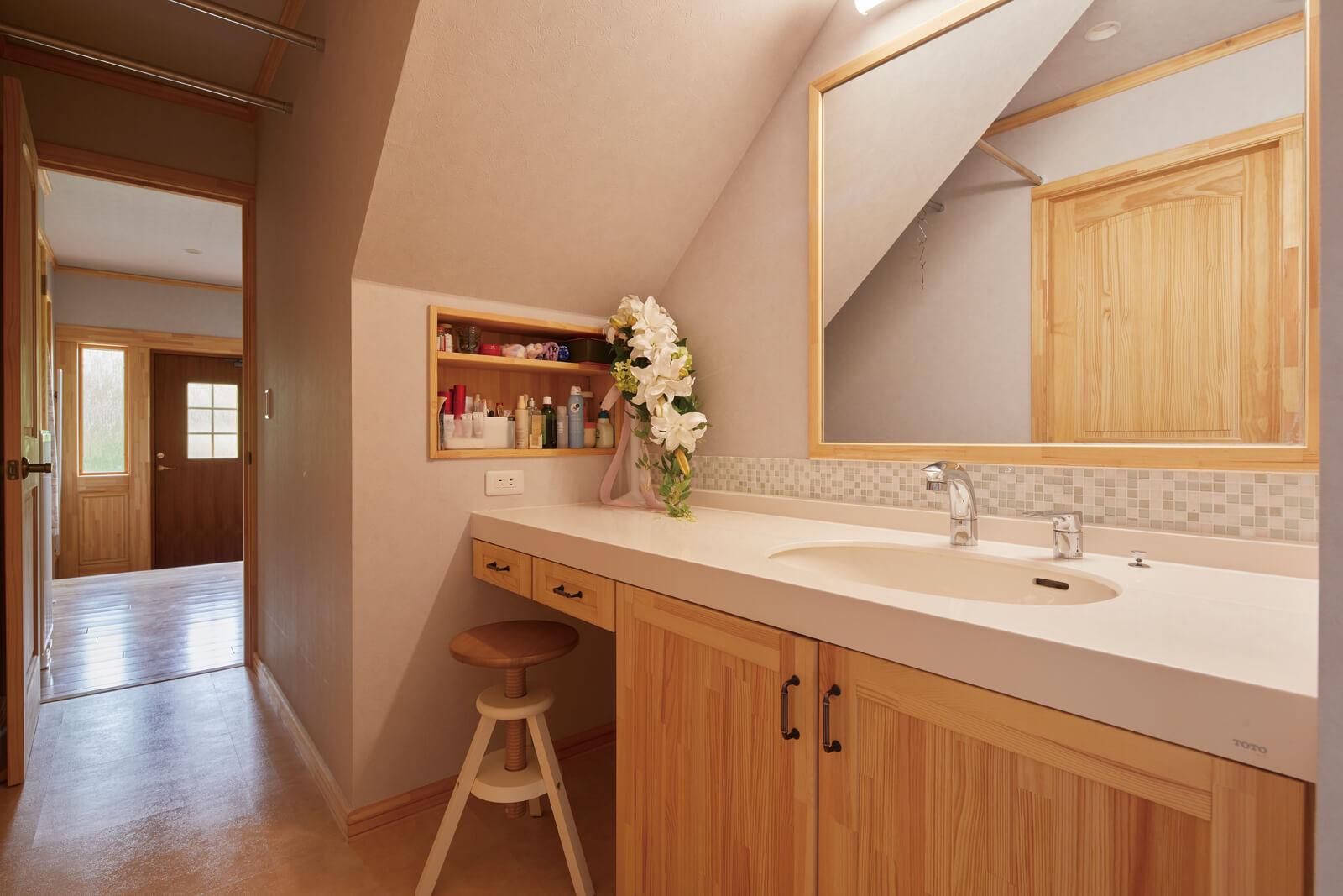 脱衣室から独立させ、裏動線に設けた洗面台は造作仕様。天井には物干しポールも設置されており、作業着なども干しやすい